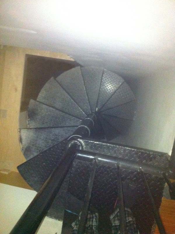 The tall, spiral staircase seemed to lead downward directly into a wall.