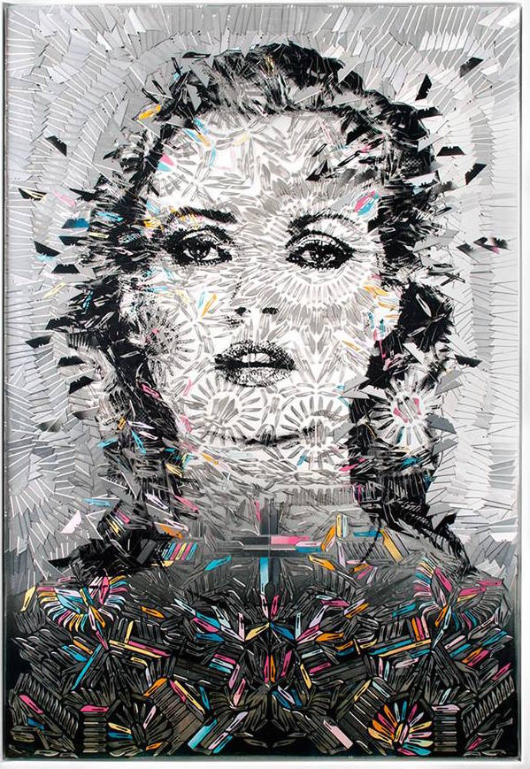 The portrait of a staring woman is decorated with ornate and complex patterns made of razor blades of varying colors and shades.